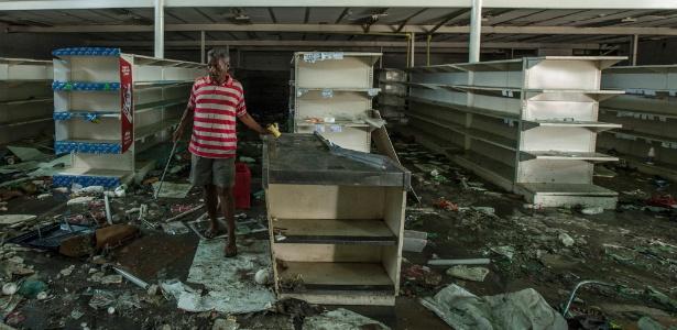 Homem procura por comida em supermercado que foi saqueado em junho, em Cumaná, na Venezuela