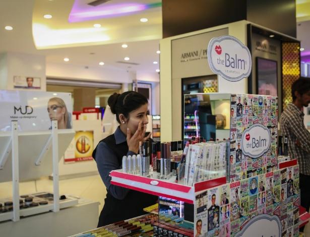 Mulher experimenta produtos cosméticos em shopping em Karachi, no Paquistão