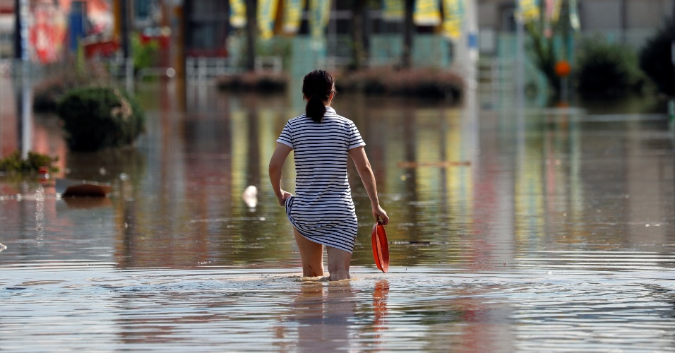 8.jul.2018 - Uma mulher faz seu caminho em uma área inundada na cidade de Kurashiki, província de Okayama