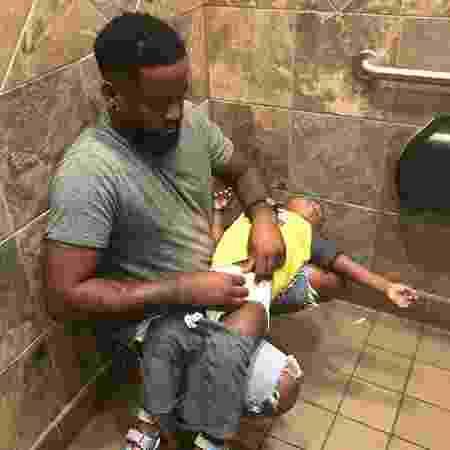 Donte Palmer, da Flórida, com dificuldade para trocar a fralda do filho dentro de um banheiro masculino - Reprodução