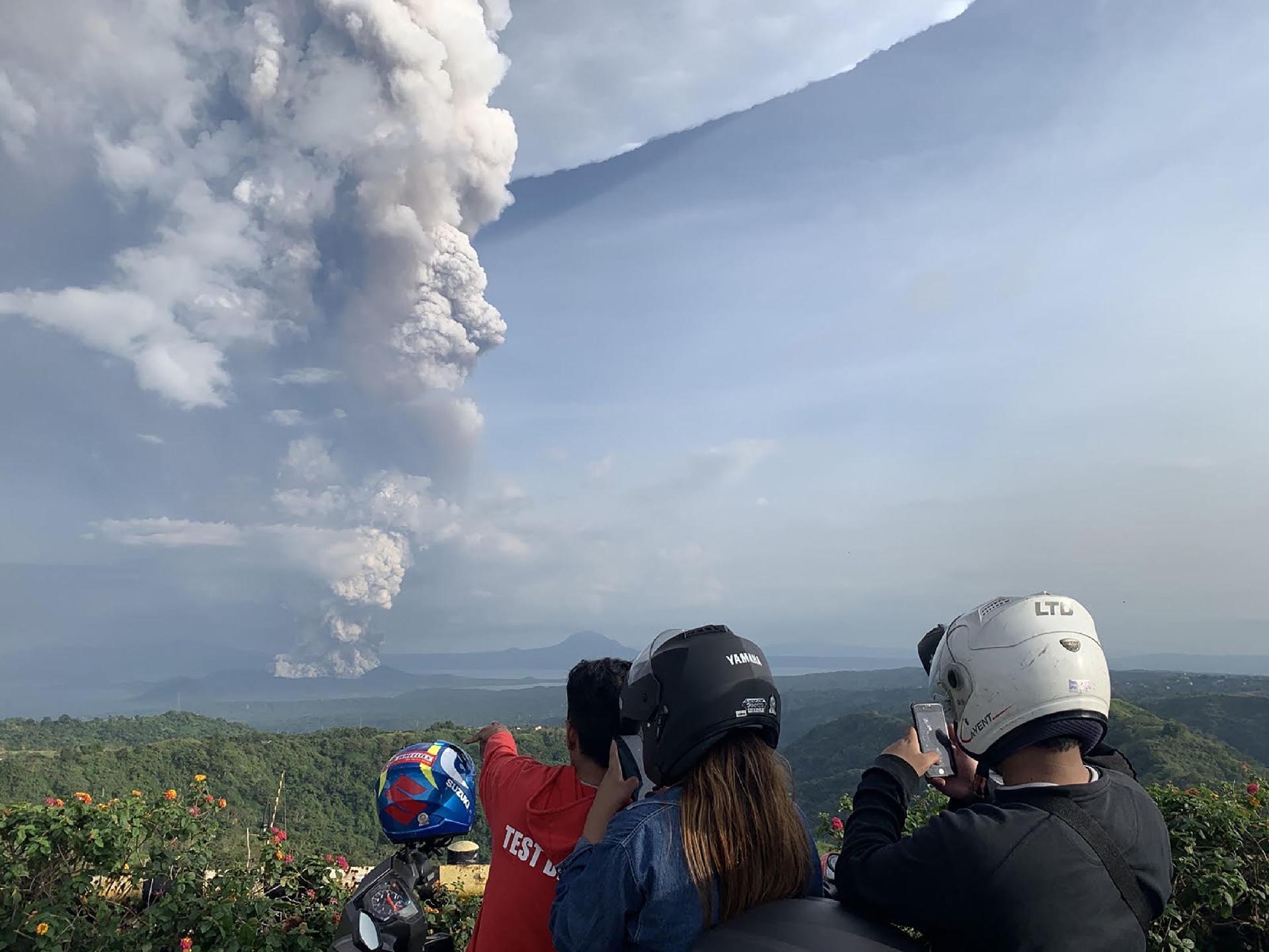 12.jan.2020 - Pessoas tiram fotos da erupção do vulcão Taal, nas Filipinas
