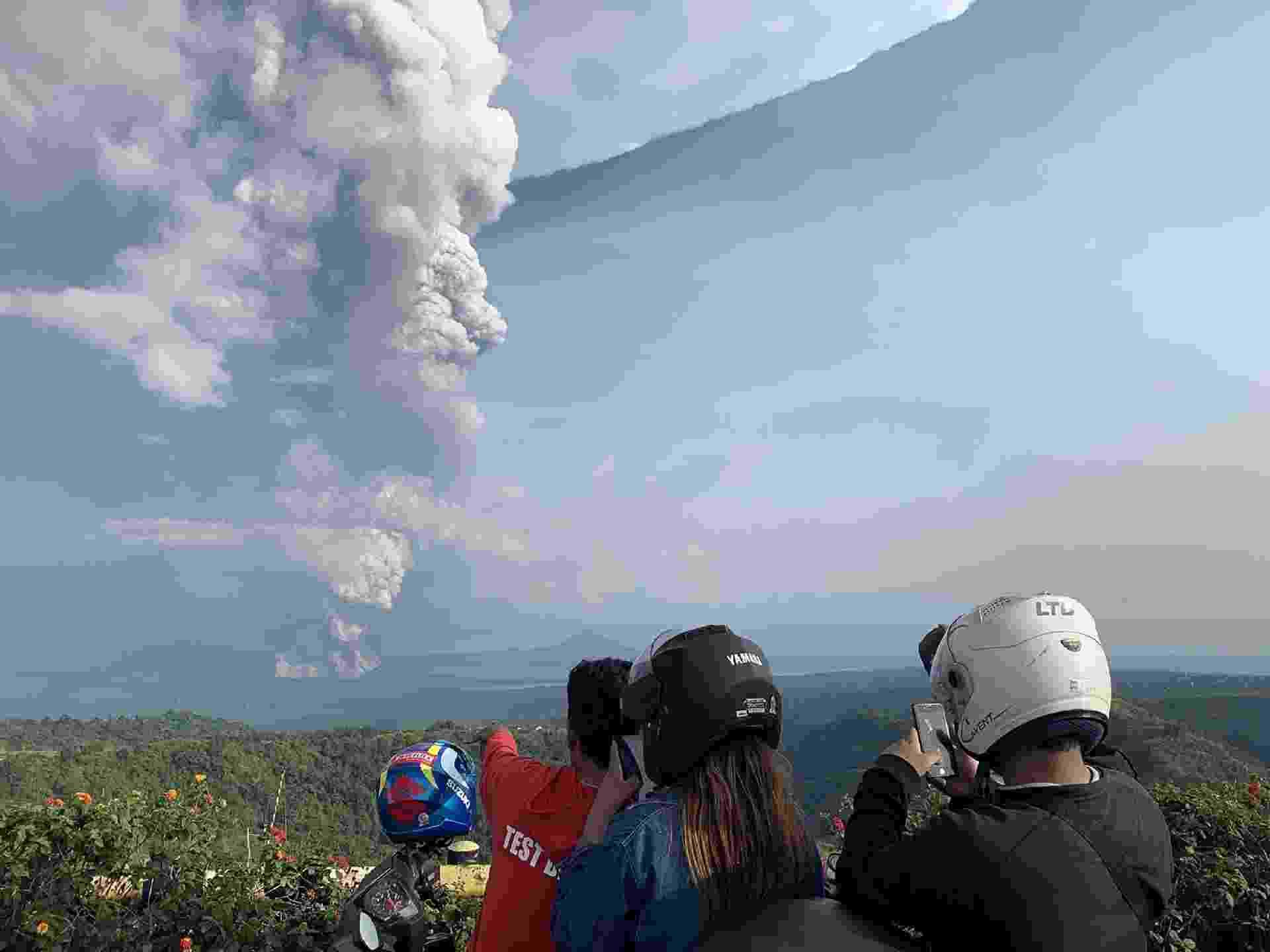 12.jan.2020 - Pessoas tiram fotos da erupção do vulcão Taal, nas Filipinas - undefined