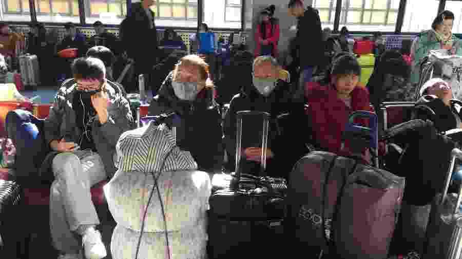 Passageiros usam máscaras para embarcar em trens na estação ferroviária oeste de Pequim - Stringer/Reuters
