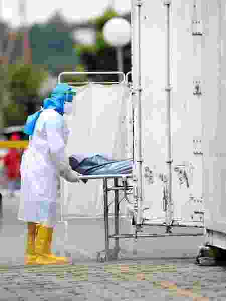 Um profissional de saúde, usando equipamento de proteção, transporta o corpo de vítima de coronavírus, no hospital Dr. João Lucio Pereira Machado, em Manaus - BRUNO KELLY/REUTERS