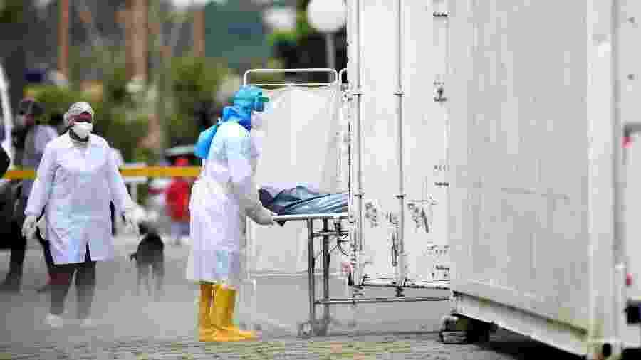 Um profissional de saúde, usando equipamento de proteção, transporta o corpo de uma pessoa para um caminhão refrigerado durante o surto de doença por coronavírus (COVID-19), no hospital Dr. João Lucio Pereira Machado, em Manaus - BRUNO KELLY/REUTERS