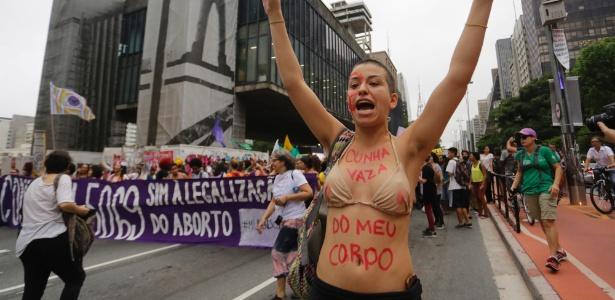 """Jovem protesta contra projeto de lei antiaborto de Eduardo Cunha usando a frase """"Cunha vaza do meu corpo"""" em manifestação em SP em novembro de 2015"""