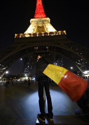 22.mar.2016 - Menino se enrola em uma bandeira da Bélgica e passeia pelo Torre Eiffel, em Paris, na França, em homenagem às vítimas que morreram durante atentado com três explosões que aconteceu em Bruxelas