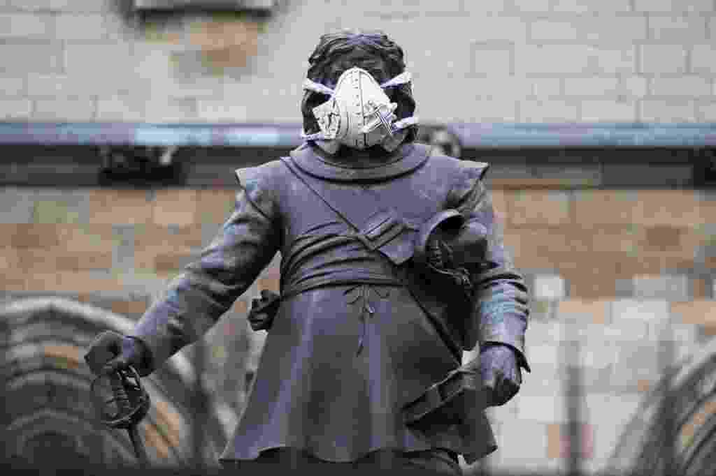 18.abr.2016 - Uma máscara de ar é fixada no rosto da estátua de Oliver Cromwell, na Casa do Parlamento britânico, em Londres. A intervenção faz parte de uma ação promovida pela ONG ambientalista Greenpeace, em que máscaras foram colocadas em estátuas famosas da capital. A ação é um alerta contra a alta concentração de poluentes no ar da cidade - Leon Neal/AFP