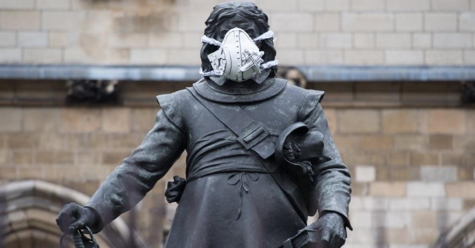 18.abr.2016 - Uma máscara de ar é fixada no rosto da estátua de Oliver Cromwell, na Casa do Parlamento britânico, em Londres. A intervenção faz parte de uma ação promovida pela ONG ambientalista Greenpeace, em que máscaras foram colocadas em estátuas famosas da capital. A ação é um alerta contra a alta concentração de poluentes no ar da cidade