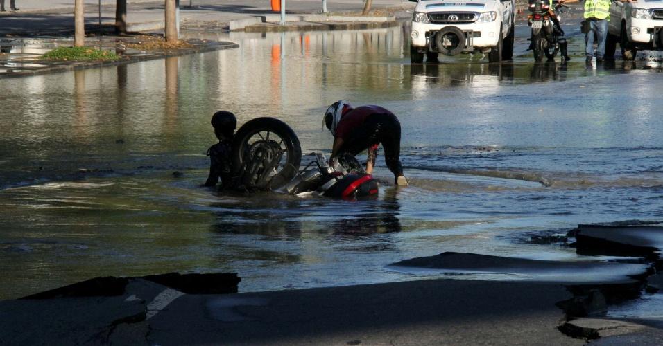 20.abr.2016 - Motociclista e passageiro caem em buraco que se abriu após rompimento de uma tubulação da Cedae que interdita os dois sentidos da Radial Oeste, zona norte do Rio de Janeiro