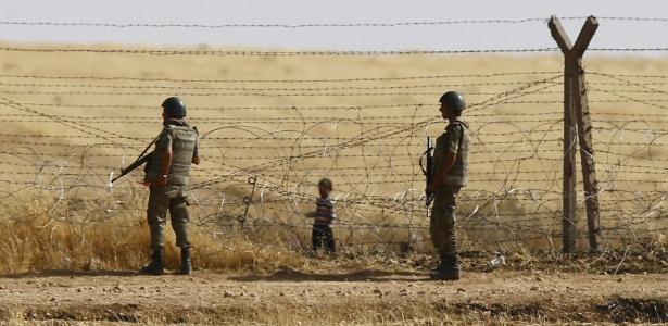Soldados turcos montam guarda enquanto menino refugiado espera atrás de cerca para atravessar para da Síria para a Turquia