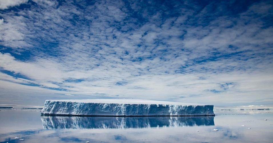 Um iceberg tabular no Oceano Ártico. Geralmente pesando bilhões de toneladas, os icebergs tabulares (em forma de tábua) são enormes planícies de gelo flutuante que se estendem por quilômetros