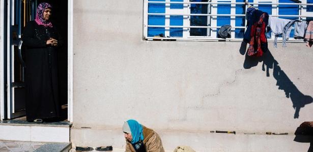 Moradores descansam na entrada de casa em Al-Intisar, a sudeste de Mossul
