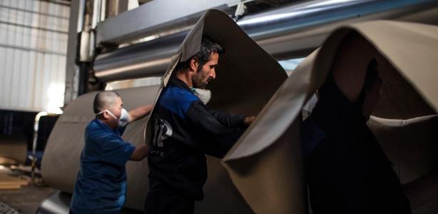 Empregados chinês e iraniano trabalham em usina de reciclagem de papel, em Neyshabur, Irã