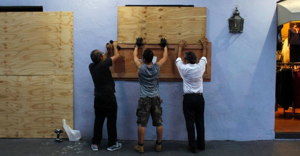 18.set.2017 - Porto-riquenhos colocam tábuas de madeira para proteger janelas antes da chegada do furacão Maria a San Juan