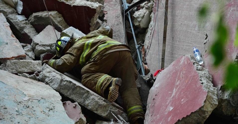 19.set.2017 - Membro de equipe de resgate busca pessoas soterradas na Cidade do México