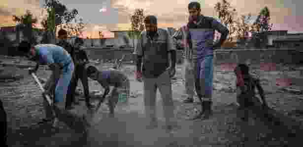 Garotos cavam para ajudar Fouad Mohammed Sadi (centro) a enterrar os membros da família - IVOR PRICKETT/NYT