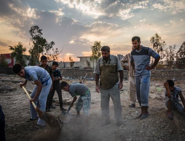 Garotos cavam para ajudar Fouad Mohammed Sadi (centro) a enterrar os membros da família