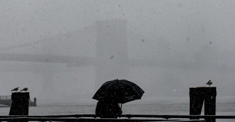 7.mar.2018 - Homem fotografa a Ponte do Brooklyn durante nevasca, em Nova York, EUA