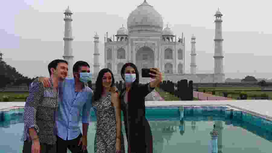 Turistas tiram fotos no Taj Mahal, na Índia. Local reabriu as portas ao público mesmo em meio à alta de casos de covid no país - Sajjad Hussain/AFP