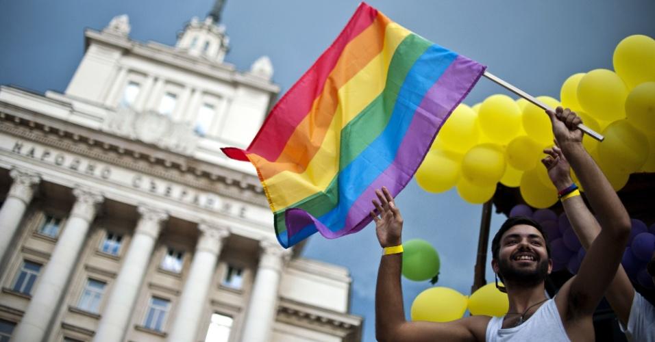 27.jun.2015 - Manifestante ergue uma bandeira de arco-íris em cima de um caminhão durante a Parada Anual do Orgulho Gay no centro de Sófia, na Bulgária, neste sábado (27). Centenas de pessoas desfilaram pela capital búlgara com balões coloridos e faixas durante a oitava parada gay da cidade. Durante o evento, grupos extremistas tentaram parar o desfile, mas os manifestantes foram escoltados pela polícia