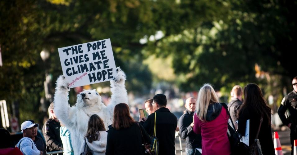 23.set.2015 - Manifestante veste fantasia de urso polar no meio da multidão que esperava o papa no National Mall, em Washington. Ele carrega um cartaz pelo qual se lê: