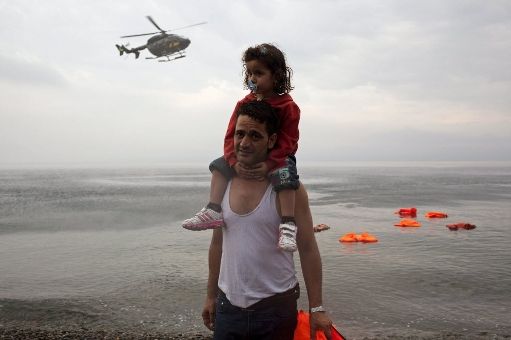 28.set.2015 - Refugiado sírio carrega sua filha após desembarcar na ilha grega da Lesbos, enquanto um helicóptero da Frontex, agência europeia responsável pela gestão das fronteiras