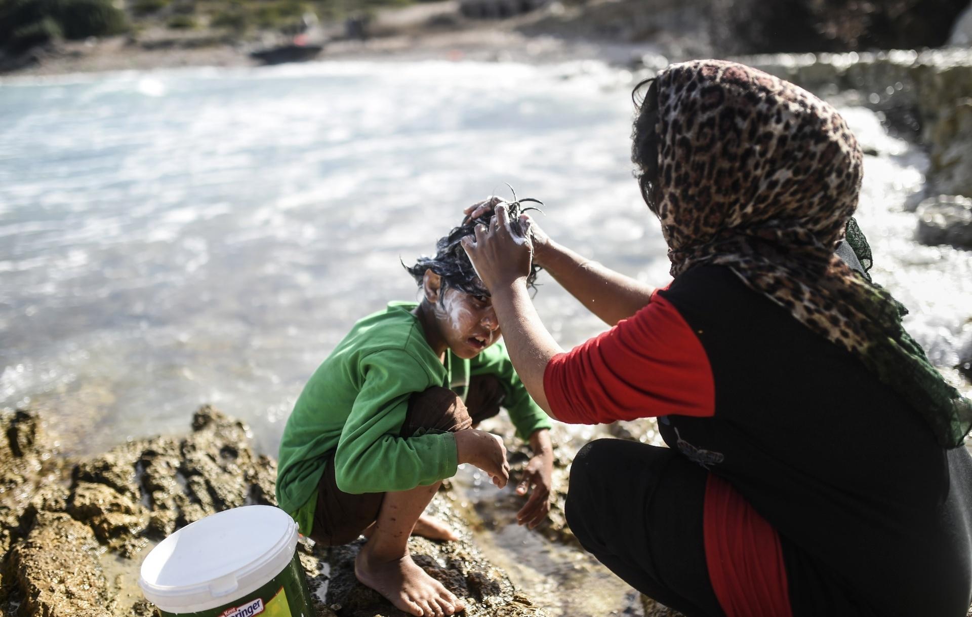 3.nov.2015 - Mãe lava o cabelo de seu filho enquanto eles esperam na província turca de Izmir para seguir viagem rumo à Grécia. A Anistia Internacional criticou o fracasso da Europa em conter as mortes de imigrantes no mar Egeu, onde milhares de refugiados atravessam da Turquia para chegar ao continente