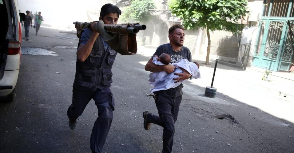 22.jul.2016 - 22.jul.2016 - Homens fogem carregando dois bebês no colo após uma sequência de ataques aéreos na cidade de Douma, Síria, que é controlada pelos rebeldes e está cercada