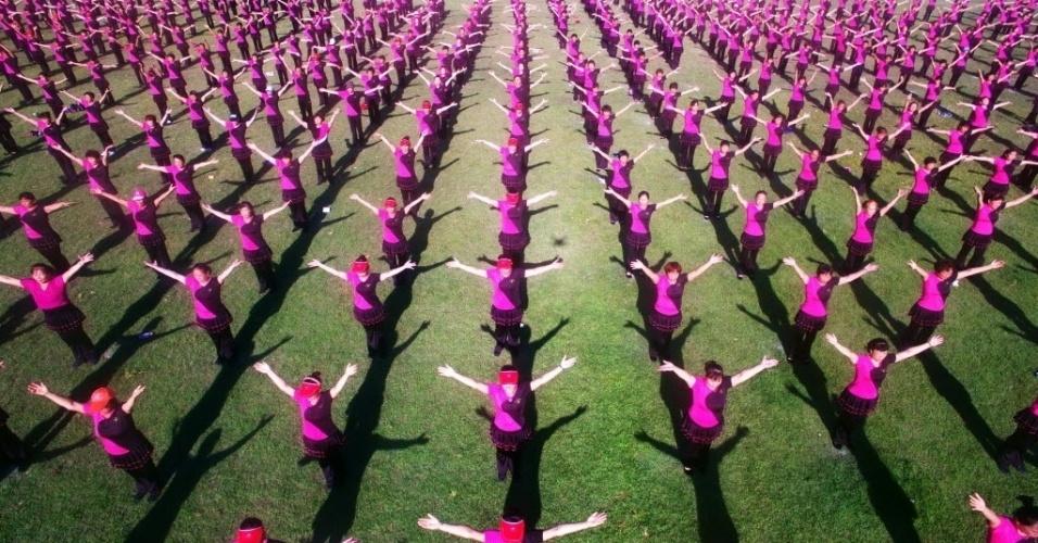 8.ago.2016 - Centenas de pessoas praticam exercícios físicos para celebrar o Dia Nacional da Ginástica, em Hainan, na China