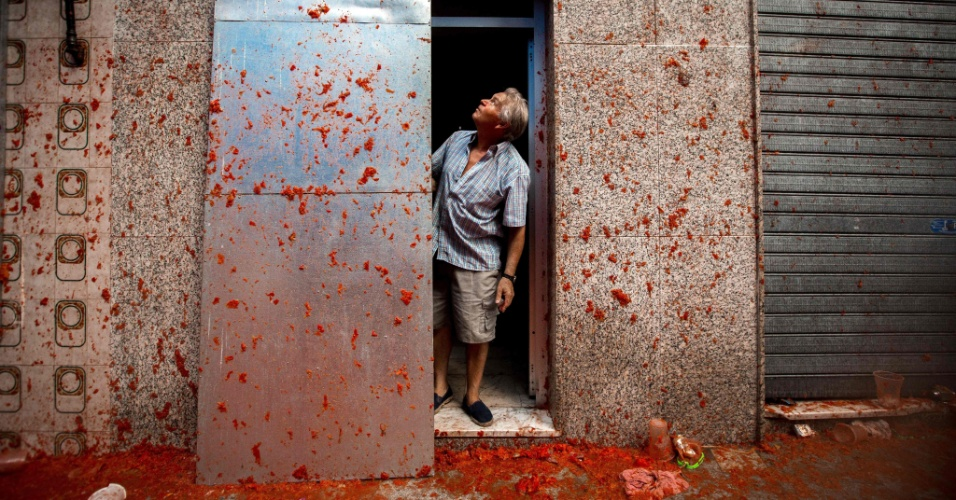 31.ago.2016 - Morador observa parede de sua casa suja com molho de tomate durante a Tomatina, em Buñol, na Espanha