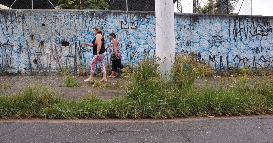 26.abr.2017 - Pedestres enfrentam o mato na rua Murmúrio da Tarde, ao lado do parque Raul Seixas, na zona leste de São Paulo