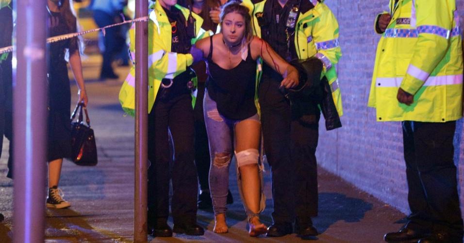 22.mai.2017 - Policiais ajudam a pessoa ferida após explosão em Manchester, na Inglaterra