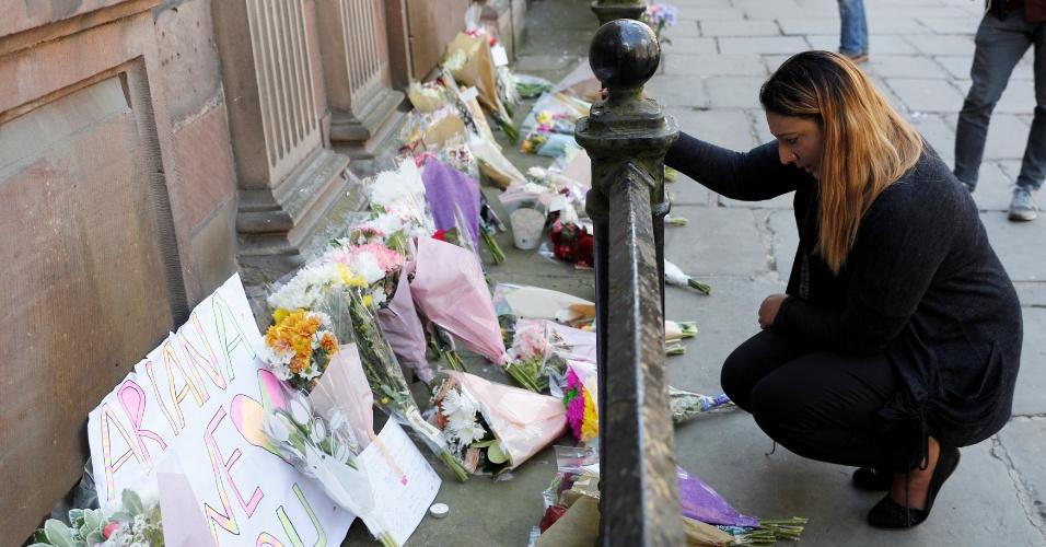 23.mai.2017 - Mulher coloca flores para as vítimas do atentado que ocorreu na Manchester Arena