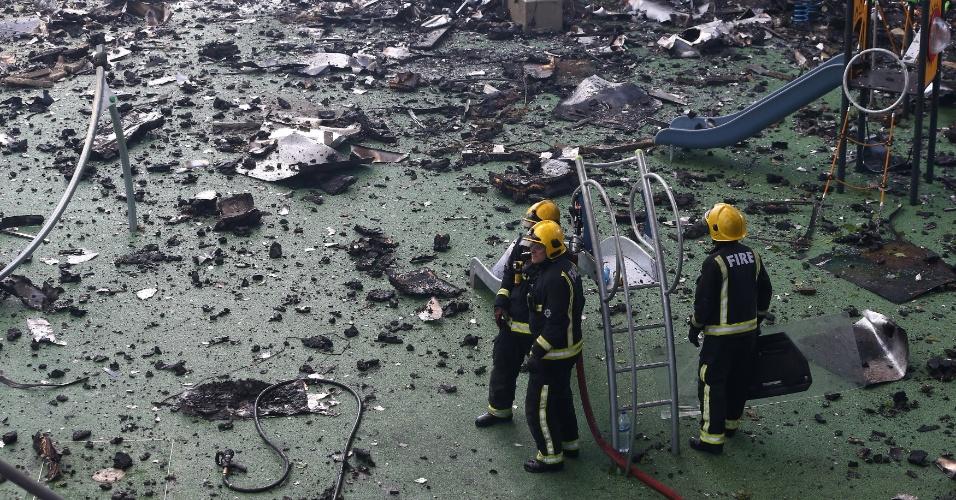 14.jun.2017 - Bombeiros em meio aos escombros de playground do prédio vizinho ao prédio que pegou fogo nesta quarta