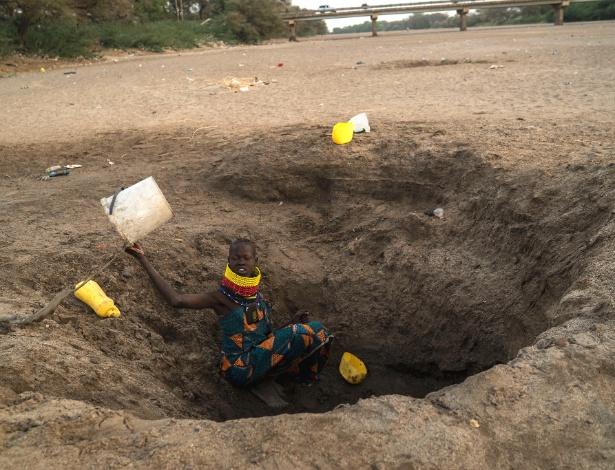 Mulher coleta água de um poço quase seco perto de Kakuma, no norte do Quênia
