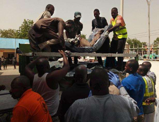 Pessoas carregam corpos para levar ao necrotério após ataque do Boko Haram no sábado (22) - Audu Marte/AFP