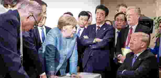 A primeira-ministra da Alemanha, Angela Merkel, e o presidente dos Estados Unidos, Donald Trump, se encaram rodeados de líderes do G7 - Jesco Denzel/AFP