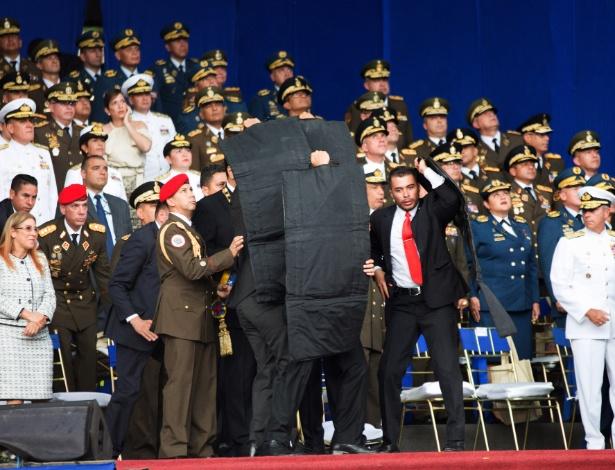 Seguranças protegem o presidente Venezuelano Nicolas Maduro depois de seu discurso ser interrompido em Caracas