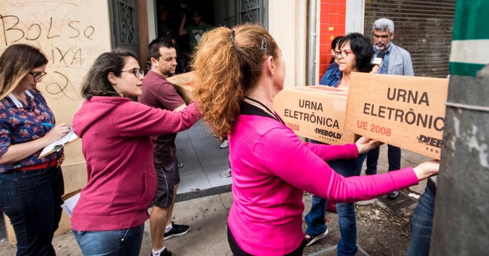 Agentes do Tribunal Regional Eleitoral (TRE), com o apoio da Policia Militar, deixam o cartório da 1ª zona eleitoral na região central da capital paulista com as urnas eletrônicas que serão distribuídas nos postos de votação de São Paulo, para o 2º turno das Eleições