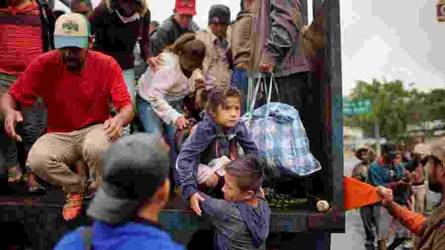 Migrantes saem de caminhão em Tierra Blanca, no México, durante viagem rumo aos EUA - Alexandre Meneghini/Reuters