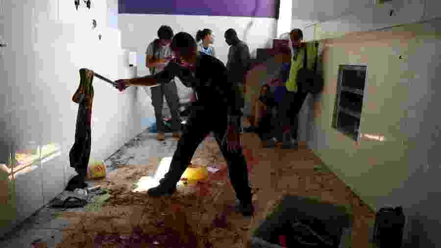 8.fev.2019 - Policial analisa local onde 14 pessoas foram mortas durante ação da polícia - Pilar Olivares/Reuters