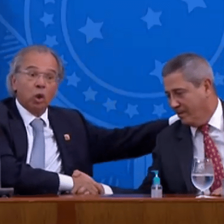 O ministro da Economia, Paulo Guedes, e o ministro-chefe da Casa Civil, Braga Netto, trocam aperto de mãos em coletiva sobre coronavírus - Reprodução/TV Brasil