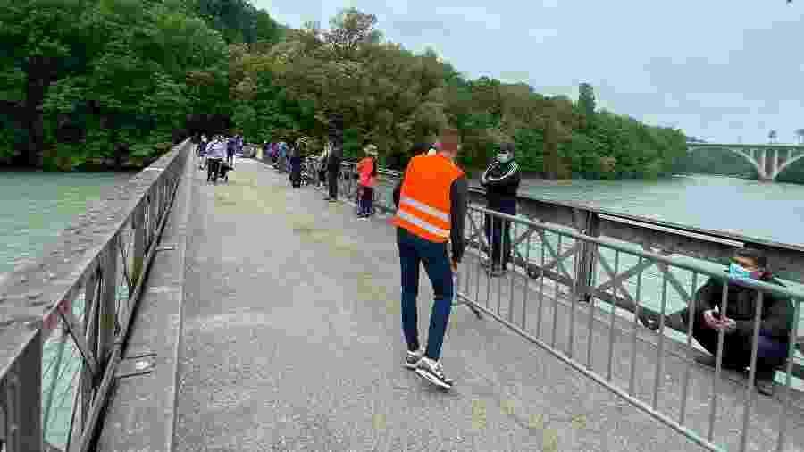 Funcionário organiza fila para receber comida na Suíça, obedecendo distanciamento na pandemia de coronavírus - Jamil Chade/UOL
