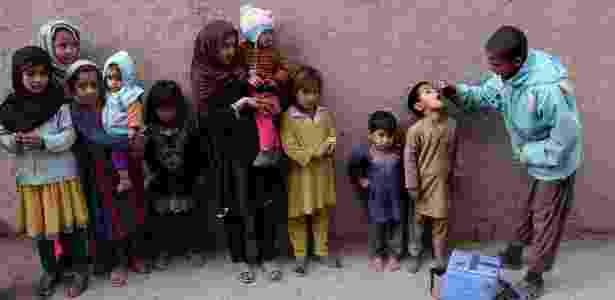 2.dez.2015 - Funcionário do setor da saúde do Afeganistão aplica vacina contra a poliomielite em criança durante campanha de vacinação nos arredores de Jalalabad, situada a cerca de 150 km da capital Cabul. A paralisia infantil é considerada endêmica em apenas três países do mundo: Afeganistão, Paquistão e Nigéria - Noorullah Shirzada/AFP - Noorullah Shirzada/AFP