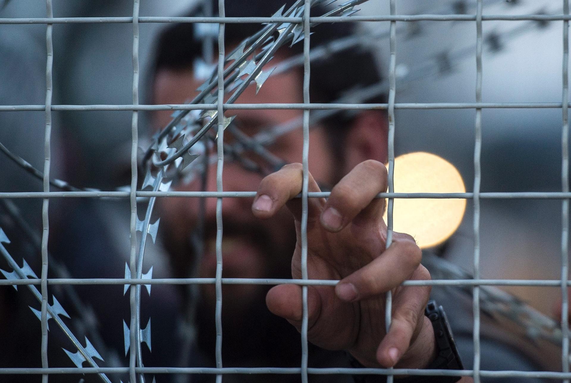 22.fev.2016 - Refugiado afegão se agarra à cerca de proteção com arame farpado na fronteira entre a Macedônia e a Grécia, próxima à cidade de Gevgelija. O Ministério de Relações Exteriores da Macedônia informou que só é liberada a passagem de