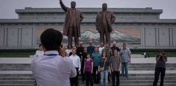 Turistas tiram foto em frente às estátuas dos ex-líderes Kim Il-Sung (esq.) e Kim Jong-Il, em Pyongyang