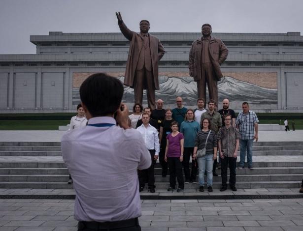Turistas tiram foto em frente às estátuas dos ex-líderes Kim Il-Sung (esq.) e Kim Jong-Il, em Pyongyang - Ed JONES /AFP