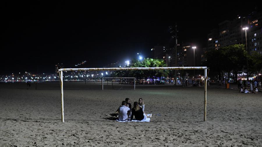 Pequeno grupo celebra a virada de ano na praia de Copacabana, no Rio - Lucas Landau / Reuters