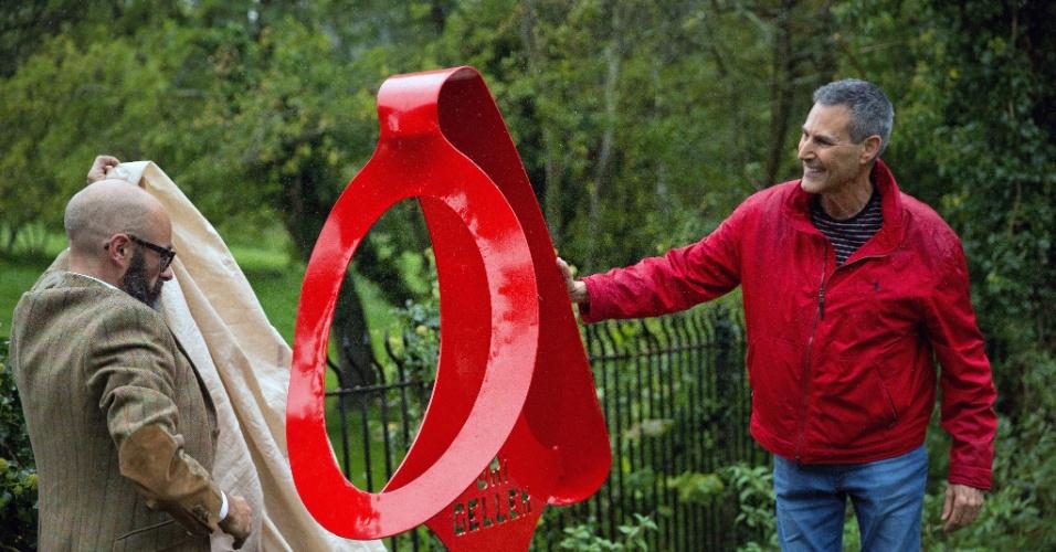 6.out.2015 - O ilusionista Uri Geller (à direita), de 68 anos, que ficou famoso por entortar colheres, inaugura uma escultura de uma colher torta no vilarejo de Sonning, em Berkshire, Inglaterra. A obra foi feita por Paul Wells